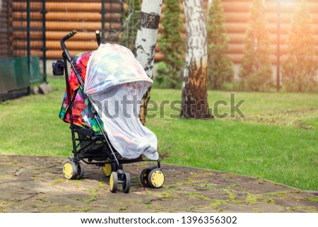Child in stroller covered with protective net during walk. Baby carriage with anti-mosquito white cover. Midge protection for children during outdoor walking season #1396356302