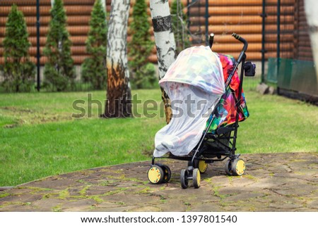 Child in stroller covered with protective net during walk. Baby carriage with anti-mosquito white cover. Midge protection for children during outdoor walking season. #1397801540