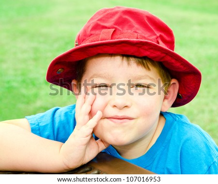 Child in summer portrait wearing bright red hat outdoors at park