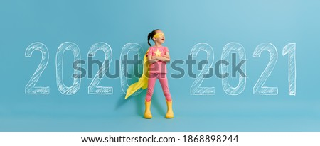 Photo of  Child in superhero costume between 2020 and 2021 years on background of wall.