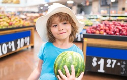 Child in supermarket hold watermelon, buying fruit and juice. Kid grocery shopping. Little boy choosing fresh vegetables in local store. Sale, consumerism and kids concept