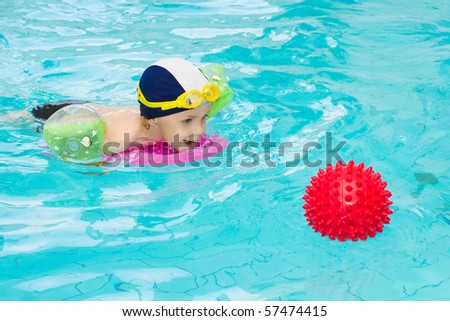 Child in swimming pool, kid swim playing water ball, little boy indoor training, 3 years old