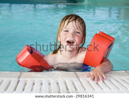 child in swimming pool with wings. toddler in water in leisure center