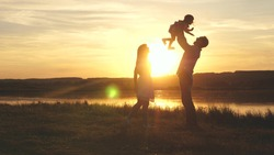 Child in the hands of parents jumps from dad to mom and laughs. Happy family walk on the beach at sunset. Child, daughter, mom, dad play fun in park in park in sun. Family fantasies, childhood dreams.