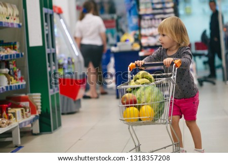 child in the store buys food