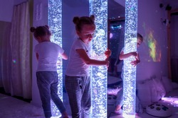 Child in therapy sensory stimulating room, snoezelen. Autistic child interacting with colored lights bubble tube lamp during therapy session.