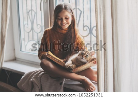 Child in warm woolen sweater seating on window sill and reading a book. Winter weekend with cat at home. Cozy scene, hygge concept.