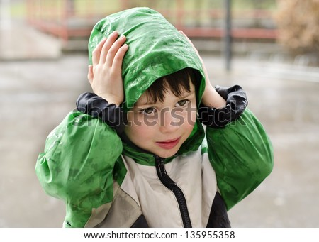 Child in waterproof jacket in the rain.