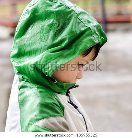 Child in waterproof jacket in the rain, profile portrait.