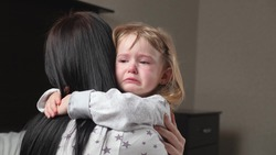 Child is crying in room in the arms of his mother. A loving young mother hugs and comforts her little daughter. Mom calms child. Family mother and baby with tears in their eyes emotionally embrace