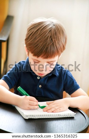 Child is drawing and painting with felt pen on paper of spiral notebook on small wooden table in living room at home. Childhood. Cute little boy and kid draws pencil and colorful markers in preschool.