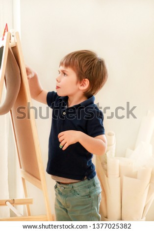 Child is drawing and painting with felt pen on paper of wooden drawing board artist easel for kids and children at home. Childhood. Cute little boy, kid draws pencil and colorful markers in preschool.