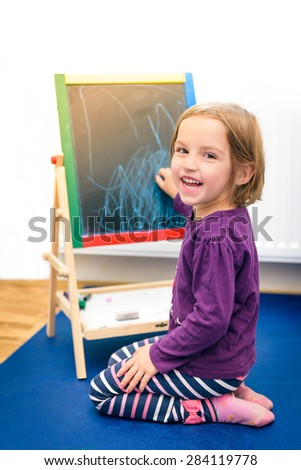 Child is drawing with pieces of color chalk on the chalk board. Girl is expressing creativity and looking at the camera, smiling in a nursery, classroom or playroom. Concept of expression and learning