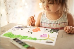 child is engaged in drawing. The concept of children's leisure and the development of creative abilities. Real interior and blur, warm toning
