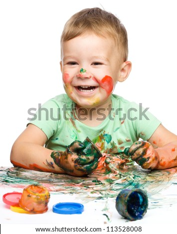 Child is grabbing some paint using fingers, isolated over white - stock photo