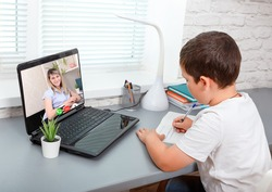 Child is having classes online, video call zoom his teacher. Cute boy is studying english language online with laptop at home. New normal. Covid-19, coronavirus. Homeschooling and distance learning