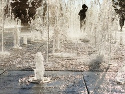 Child Is Having Fun In Dry Fountain Splashes Water On Hot Sunny Day