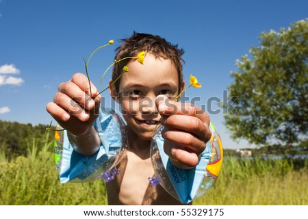child is holding field flowers on warm summer day