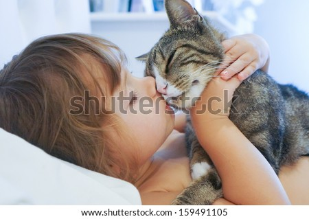 Child is kissing a cat