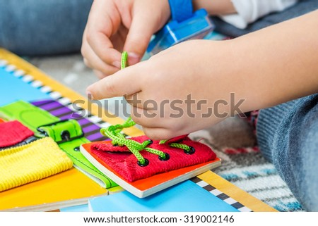 child is learning to tie the laces with a special toy #319002146