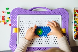 Child is playing with mosaic puzzle at home. Children's creative game for early development and fine motor skills.