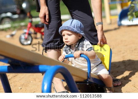 Child is sitting on a seesaw at the playground
