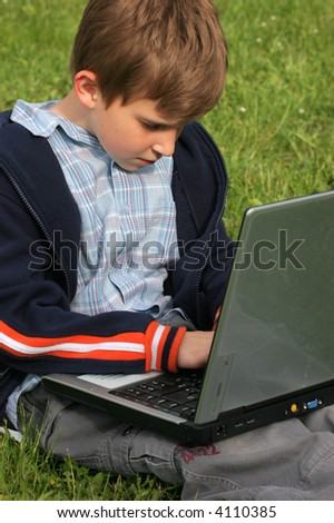 Child is sitting with laptop in the park