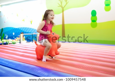 Child jumping on colorful playground trampoline. Kids jump in inflatable bounce castle on kindergarten birthday party. Activity and play center for young child. Little girl playing.
