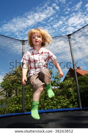 child jumping on trampoline. toddler in garden is active playing and jump