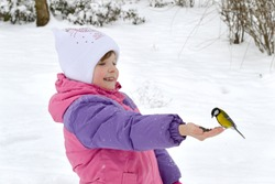 child, kid feeds small birds from the hands in the winter forest.Lifestyle of entertainment, leisure, games in the winter.