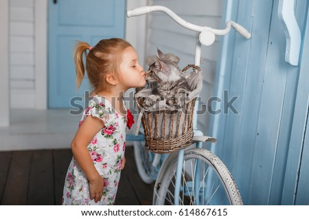 Child kiss a cat. Little girl have fun with kitten