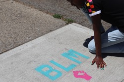 Child kneeling near BLM Blaack Lives Matter words on Sidewalk