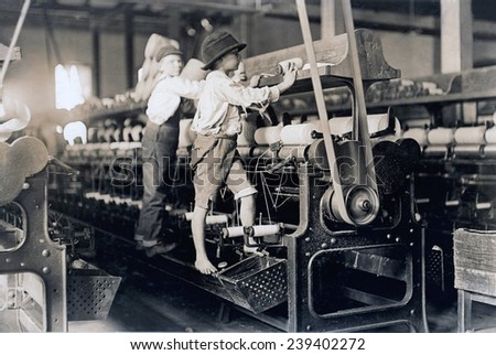 Child laborer portrayed by Lewis Hine in 1909. Barefooted boy in a George cotton mill was so small he had to climb up on the spinning frame to mend the broken threads and put back the empty bobbins.