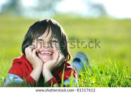 Child laying on meadow, boy at green grass in nature