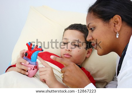 Child laying sick in bed at the hospital with doctor
