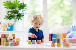 Child learning letters and numbers. Kid with colorful wooden abc blocks. Little boy spelling words with educational block toys. Kids doing school homework at white desk. Bedroom for preschool children