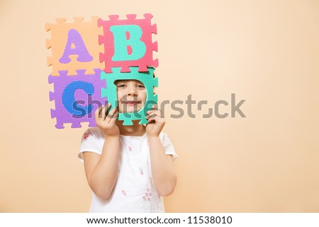 child learning the ABC's. The focus is on her eyes