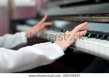 Child learning to play the piano.