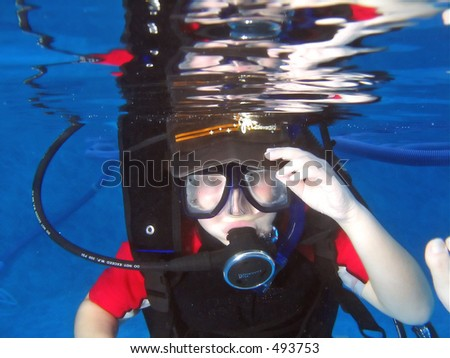 Child learning to scuba dive, having fun in pool - stock photo