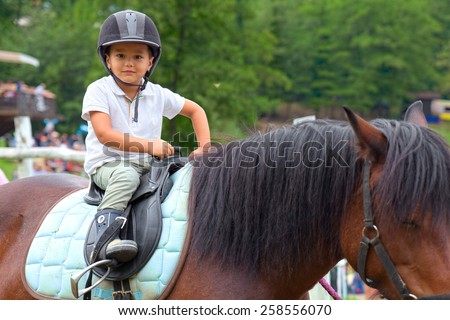 Child learns to ride a horse in a riding school of Tuscany Alps