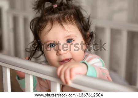 child learns to walk, baby girl in bed smiling, children's room, textiles for children's room #1367612504