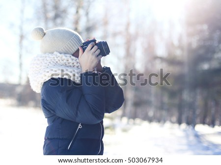 Child little boy photographer takes picture on the digital camera outdoors in winter sunny day over blurred forest background, view profile