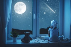 child little girl at the window dreaming the starry sky at bedtime night