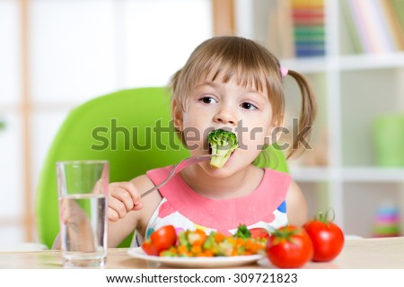 Child little girl eats vegetable salad using fork #309721823