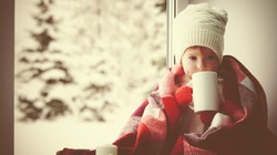 child little girl sitting by the window with a cup of hot tea and looking at the winter forest