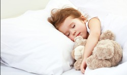child little girl sleeps in the bed with a toy teddy bear