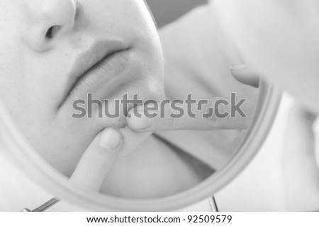 Child looking in mirror picking at pimple
