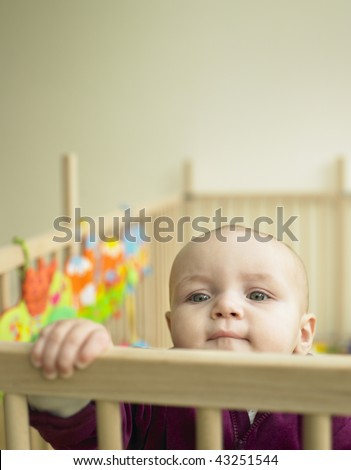 Child looking over the top of playpen. Vertically framed shot.
