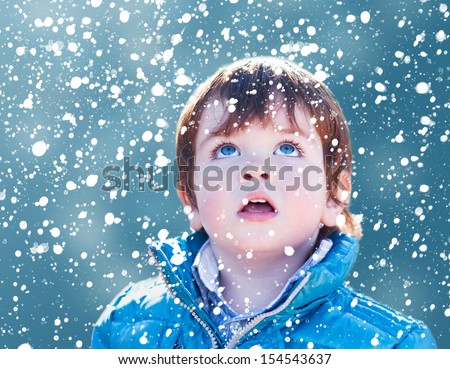 Child looking snow falling with his mouth open