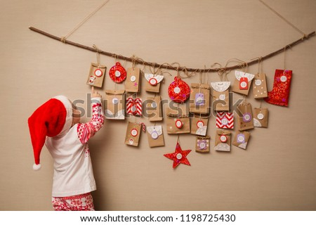 child looks at the advent calendar. Baby girl in a Christmas hat and pajamas shows on first gift.